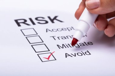 Close-up Of A Woman's Hand Ticking Avoid Option On Risk Form With Marker