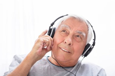 Portrait Of A Senior Man Listening To Music On Headphone At Home