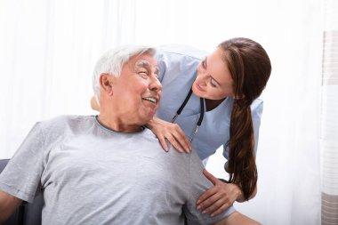 Portrait Of A Happy Female Nurse Looking At Senior Man