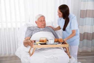 Young Female Nurse Serving Food To Senior Male Patient