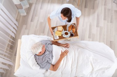 Overhead View Of Female Nurse Serving Food To Senior Male Patient In Clinic
