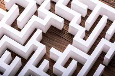Overhead View Of Abstract White Maze On Wooden Background