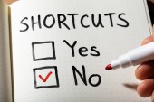 Fotografie A Person Holding Marker Over Notebook With Shortcuts Word Showing Yes And No Option