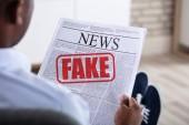 Detail africký muž, který držel noviny s falešnými zprávami