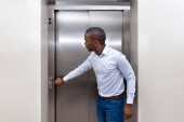 Fényképek Afrikai fiatalember, várakozás-re egy lift gomb megnyomásával