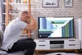 Frusztrált fiatalember ül a kanapén közel Broken TV képernyő