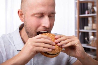 Close-up Of A Young Man Eating Fresh Burger