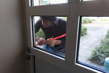 Thief Standing Behind Door Breaking With Crowbar