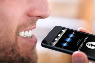 Close-up Of A Happy Man Using Voice Recognition Function On Mobile Phone