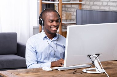 Happy African Man Using Headphone While Working On Computer Over Wooden Desk