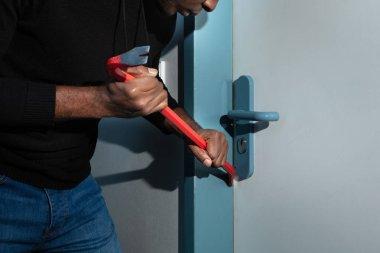 Thief In Black Hooded Sweatshirt Trying To Break The Door With Crowbar