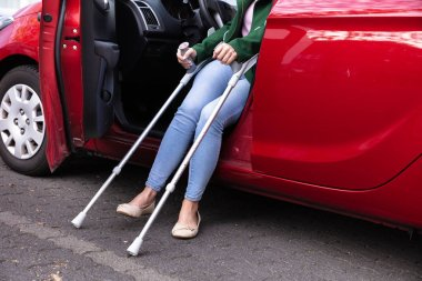 Disabled Woman With Crutches Coming Out Of A Red Car