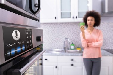 Close-up Of An Oven With Voice Recognition Function Near The Blurred Woman Standing In Kitchen