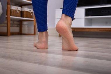 Close-up Of A Woman's Feet Walking On The Hardwood Warm Floor