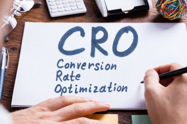 Close-up Of A Person's Hand Writing Conversion Rate Optimization On Chequered Book
