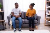 ein junges afrikanisches Paar sitzt auf dem Sofa und schaut sich an