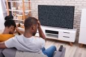 Fiatal afrikai pár ül a kanapén TV nincs jel közelében