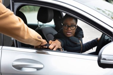 Young African Woman Stopping Thief From Stealing Suitcase While Driving Car