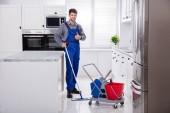 Mužské školník čištění podlahy s mopem v kuchyni