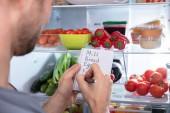 Fényképek A fiatalember írás bevásárló lista közelében nyitott hűtőszekrény