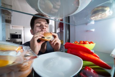Close-up Of A Hungry Young Man Eating Burger Near Refrigerator