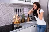 Šokoval mladá žena při pohledu na vaření hrnec hořící ohněm na indukční sporák
