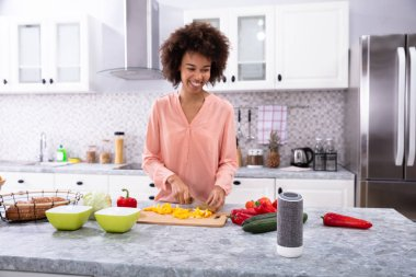 Young Happy African Woman Cutting Yellow Bell Pepper On Chopping Board In The Kitchen