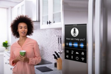 Young Woman Holding Green Coffee In Hand Looking At Refrigerator With Voice Recognition Function