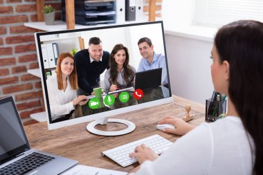Side View Of A Young Businesswoman Videoconferencing With Her Colleagues On Computer