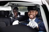 Geschäftsfrau sitzt hinter glücklichem afrikanischen Chauffeur am Steuer