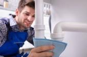 Detailní záběr na mužského instalatéra drží modrý ubrousek zastavit únik potrubí