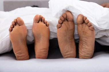 Close-up Of Couple's Bare Feet Under White Blanket