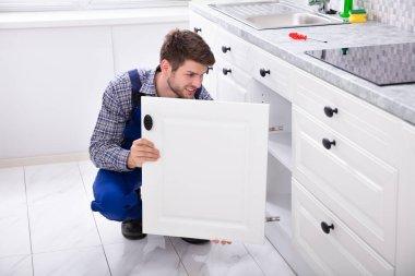 Smiling Handyman Fitting A New Door Under The Kitchen Worktop