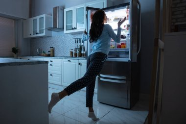 Woman Opening Refrigerator Door With Various Food In Kitchen