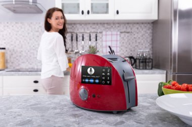 Happy Woman Looking At Red Toaster With Voice Recognition Function On Kitchen Counter