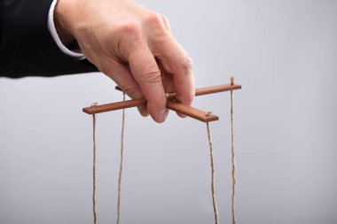 Close-up Of A Businessperson's Hand Manipulating Marionette With A String