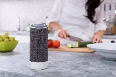 Close-up Of Voice Assistant Speaker In Front Of Woman Cutting Vegetables In Kitchen