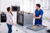 Repair Reparatur Backofen auf Küchenarbeitsplatte vor Frau lächelnd