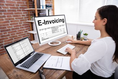 Close-up Of A Businesswoman Preparing E-invoicing Bill On Computer Over Wooden Desk