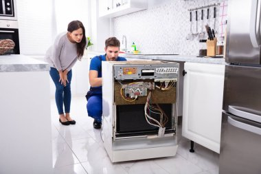 Smiling Woman Behind Technician Repairing Dishwasher In Kitchen