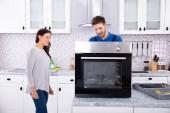 Fotografie Lächelnder Reparateur repariert Ofen auf Küchenarbeitsplatte vor Frau
