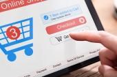 Die Hand der Person beim Online-Shopping auf dem Tablet mit dem Einkaufswagen auf dem Bildschirm