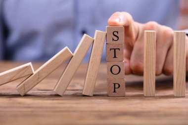Businessperson's Finger Over Wooden Blocks With Stop Text Stopping Falling Dominos On Wooden Desk
