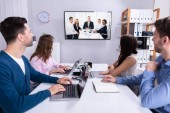 Fotografie Rear View Of Businesspeople Attending Videoconference Meeting In Office