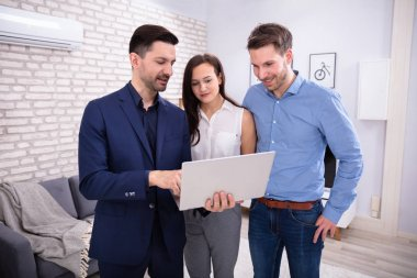 Male Realtor Showing New House To Couple In Laptop Inside A New House