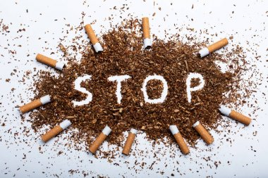 An Elevated View Of Frame Made With Broken Cigarettes Around Stop Word Written On Tobacco