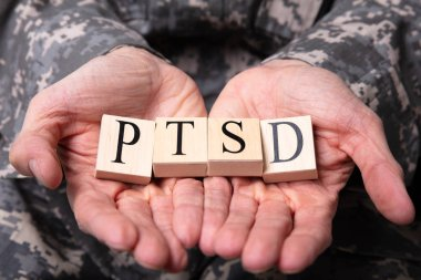 Close-up Of Male Soldier In Military Uniform Holding Wooden Cubes With PTSD Text