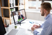 Seitenansicht von Geschäftsmann-Videokonferenzen mit Kollegen am Desktop-PC am Bürotisch