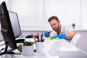 Hausmeister putzt weißen Schreibtisch in modernem Büro