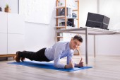 Smiling Young Businessman Exercising At Office Showing Thumb Up